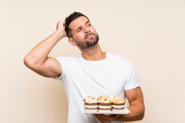 Homem bonito, segurando o bolo muffin sobre parede isolada, tendo dúvidas e com a expressão do rosto confuso