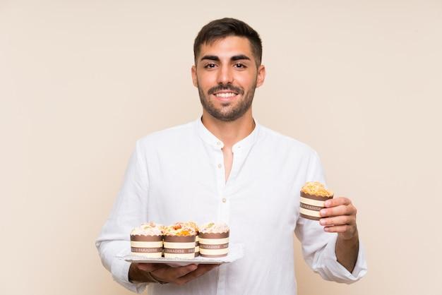 Homem bonito, segurando o bolo muffin sobre parede isolada