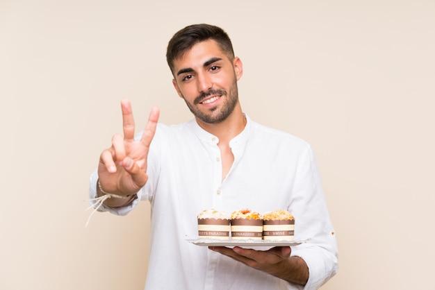 Homem bonito, segurando o bolo queque sobre parede isolada, sorrindo e mostrando sinal de vitória