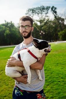 Homem bonito, segurando o bulldog francês, andando no parque