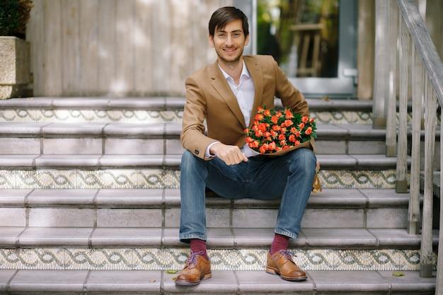 Homem bonito, segurando o buquê de rosas