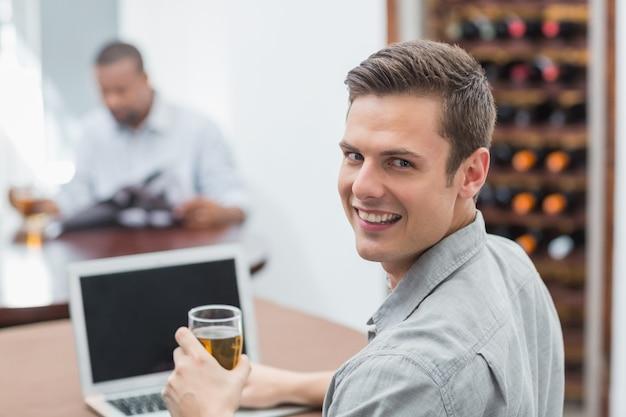 Homem bonito, segurando o copo de cerveja enquanto estiver usando o laptop