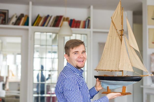 Homem bonito segurando o layout de um veleiro
