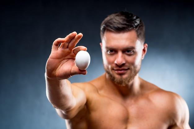 Homem bonito segurando ovo cru nas mãos, mostrando para a câmera