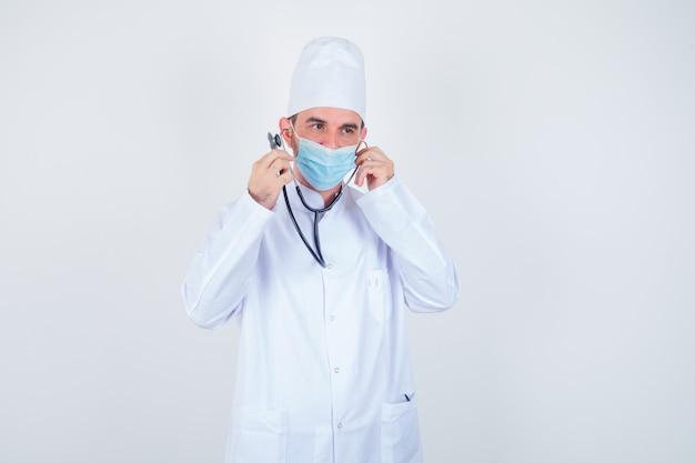 Homem bonito, segurando pedaços de orelha do estetoscópio nas orelhas, como se estivesse ouvindo com o jaleco branco de laboratório médico, máscara e parecendo feliz, vista frontal.