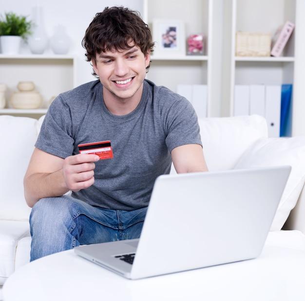 Homem bonito segurando um cartão de crédito e usando o laptop para fazer compras online - dentro de casa