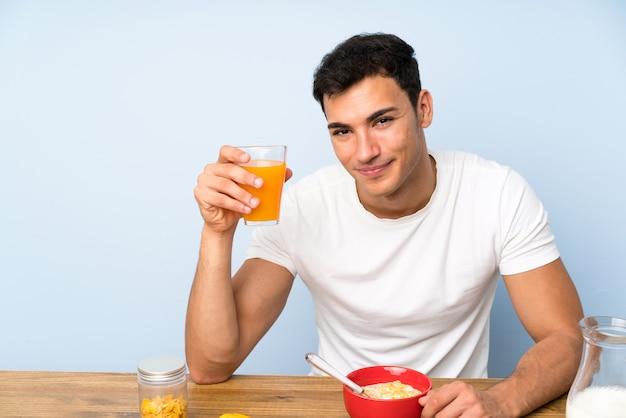 Homem bonito, segurando um suco de laranja