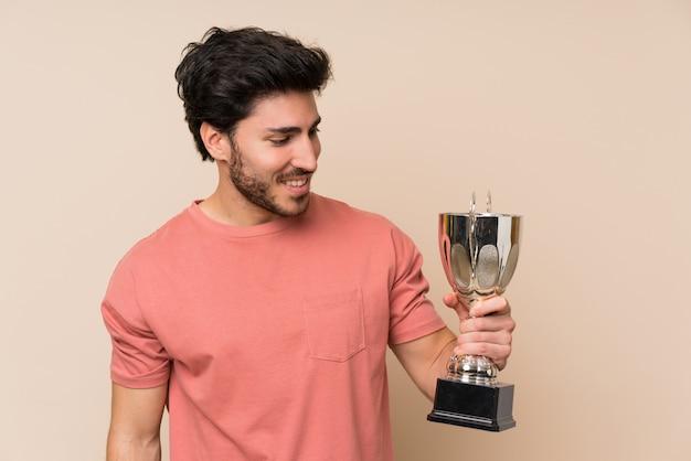 Homem bonito, segurando um troféu