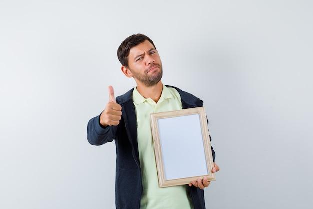 Homem bonito segurando uma moldura em uma roupa casual