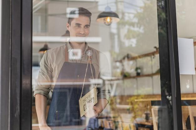 Homem bonito segurando uma placa na frente de uma loja, um funcionário do café segurando uma placa dizendo abre-fecha, ele está virando uma placa dizendo