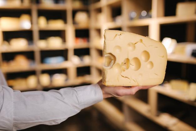 Homem bonito segurar grande fatia de queijo maasdam na mão. queijo com grandes buracos. fundo de prateleiras com queijo