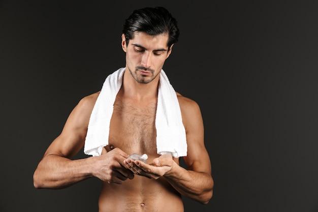Homem bonito sem camisa com toalha nos ombros, isolado, aplicando loção pós-barba