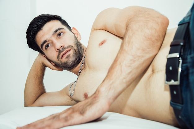 Homem bonito sem camisa, deitado na cama e ter pensamentos positivos com o olhar para longe. atitude sedutora e conceito sexy de atitude agradável
