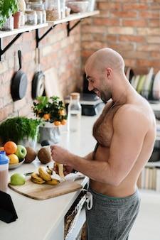Homem bonito sem camisa na cozinha