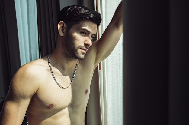 Homem bonito sem camisa tem pensamento positivo ao ficar perto da janela e desviar o olhar. atitude sedutora e conceito de atitude agradável