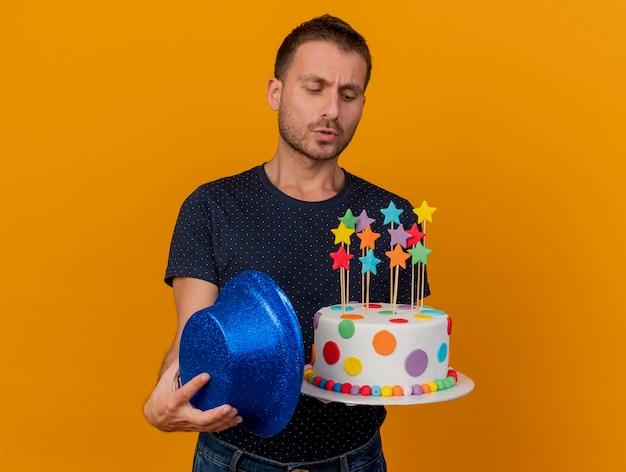 Homem bonito sem noção segurando um chapéu de festa azul e olhando para um bolo de aniversário isolado em uma parede laranja