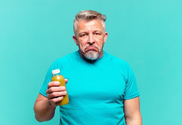 Homem bonito sênior bebendo um smoothy vegano
