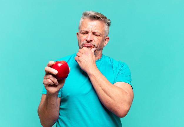 Homem bonito sênior com uma maçã