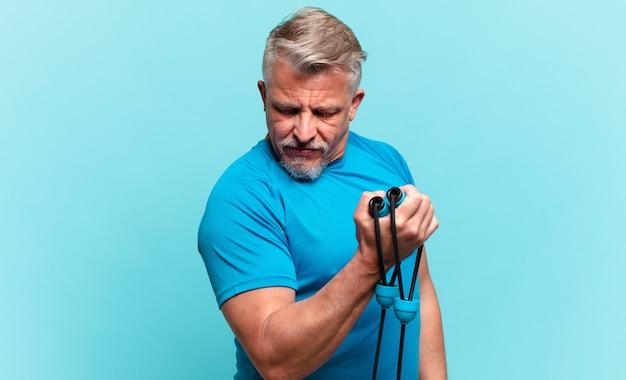 Homem bonito sênior praticando fitness e vestindo roupas esportivas