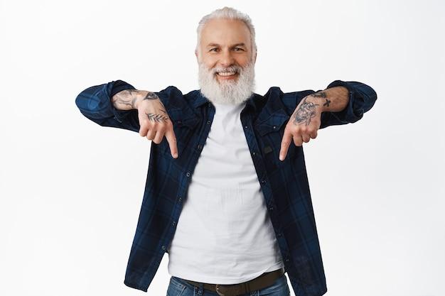Homem bonito sênior sorridente, velho hippie com tatuagens apontando os dedos abaixo, mostrando um anúncio na parte inferior com uma carinha feliz, em pé sobre uma parede branca