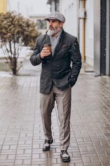 Homem bonito sênior tomando café na rua