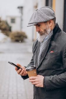 Homem bonito sênior tomando café na rua Foto gratuita