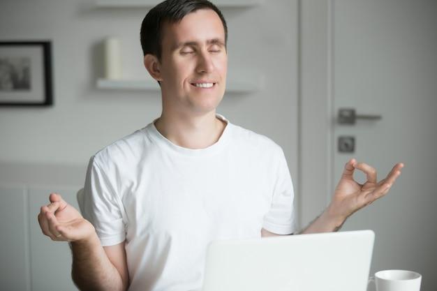 Homem bonito sentado em pose de yoga perto da mesa com laptop
