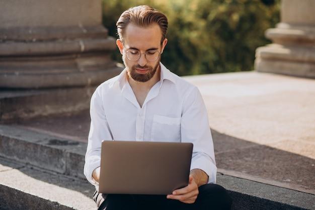 Homem bonito sentado na escada e trabalhando no computador