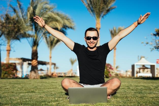 Homem bonito sentado na grama e usar o laptop com as mãos erguidas de vitória.
