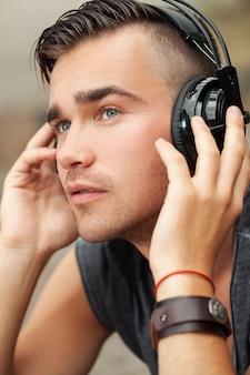 Homem bonito sentado na rua com fones de ouvido