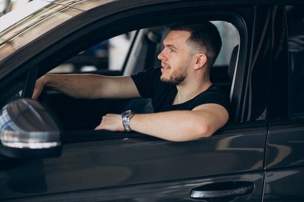 Homem bonito sentado no carro e testá-lo
