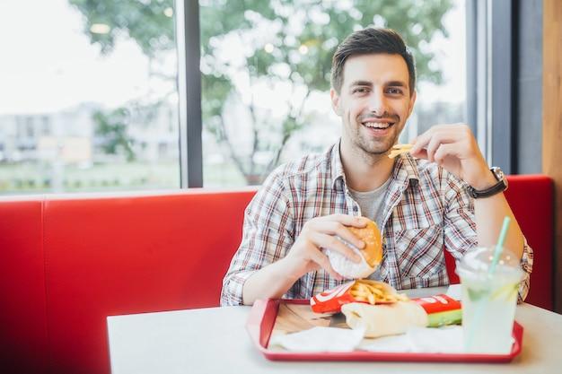 Homem bonito sentado no restaurante moderno fast-food e jantar