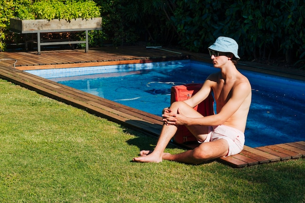 Homem bonito sentado perto da piscina com saco de bagagem e posando