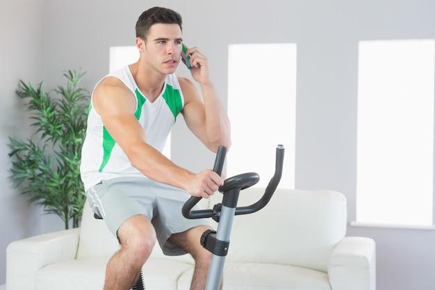 Homem bonito sério formação em bicicleta de exercício telefonando