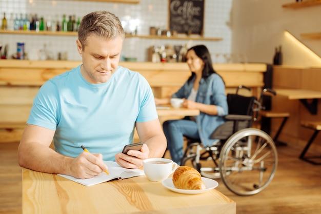Homem bonito, sério, loiro e bem constituído, segurando seu telefone e escrevendo em seu caderno, enquanto uma mulher sentada em uma cadeira de rodas ao fundo