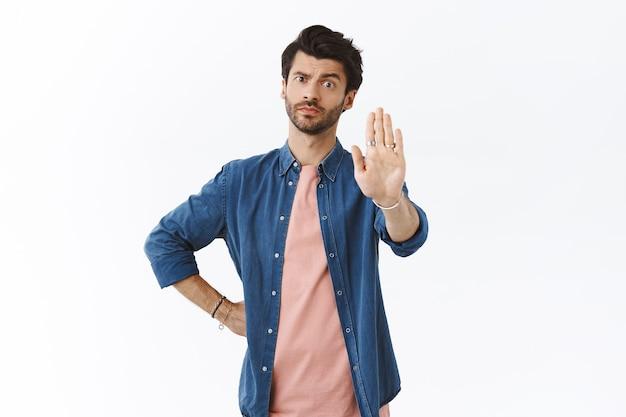 Homem bonito, sério, preocupado e assertivo, levanta um braço em proibição, movimento de advertência, sorri aborrecido e parece cético, crítico para a câmera, proíbe algo