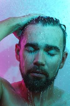 Homem bonito sob o fluxo de água em luz de néon