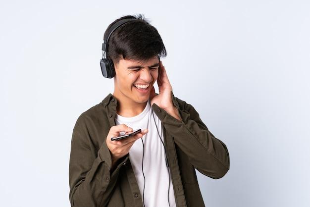 Homem bonito sobre música azul isolada com um celular e cantando