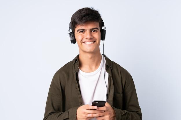 Homem bonito sobre música de fundo azul isolado com um celular e olhando de frente