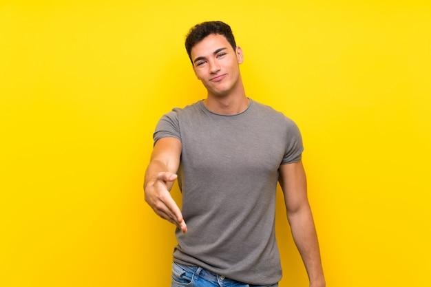 Homem bonito sobre parede amarela isolada, apertando as mãos para fechar um bom negócio