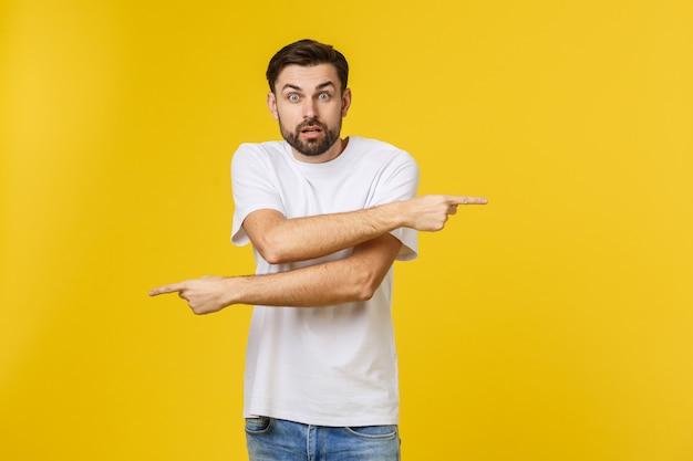 Homem bonito sobre parede amarela isolada frustrado e apontando para a frente.