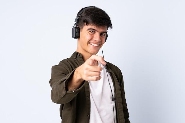 Homem bonito sobre parede azul, ouvindo música e apontando para a frente