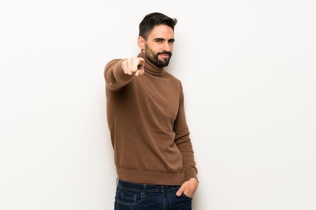 Homem bonito sobre parede branca aponta o dedo para você com uma expressão confiante