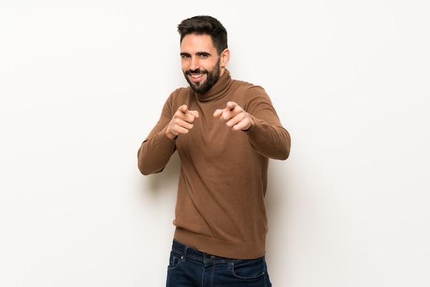 Homem bonito sobre parede branca aponta o dedo para você enquanto sorrindo