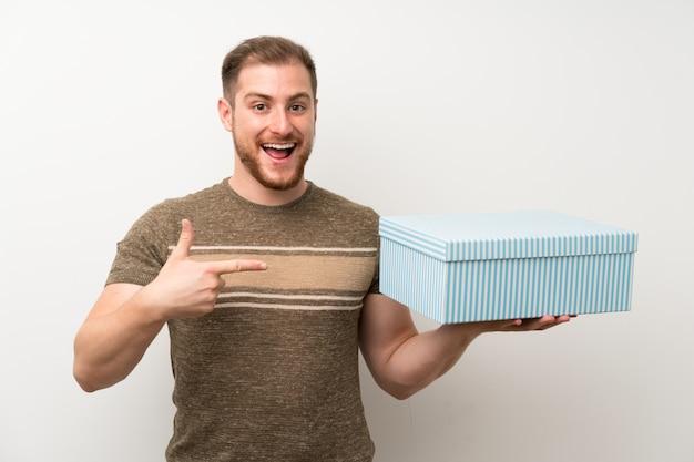 Homem bonito sobre parede branca isolada, segurando a caixa de presente