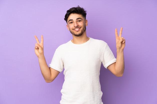 Homem bonito sobre parede isolada, mostrando sinal de vitória com as duas mãos
