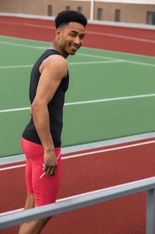 Homem bonito sorridente atleta africano na pista de corrida