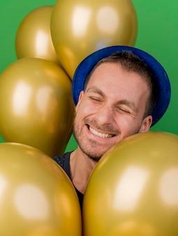 Homem bonito sorridente e satisfeito com chapéu de festa azul e balões de hélio isolados na parede verde com espaço de cópia