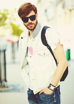 Homem bonito sorridente engraçado hipster em roupas de verão elegante na rua em óculos de sol