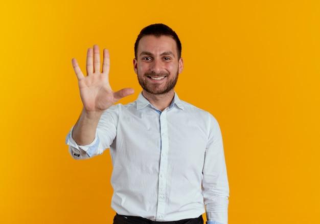 Homem bonito sorridente gesticula cinco com a mão isolada na parede laranja